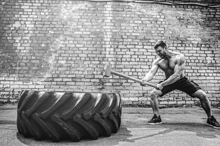 Sport Fitness Man Hitting Wheel Tire With Hammer Sledge Crossfit Training, Young Healthy Guy Gym Interior OUTSIDE
