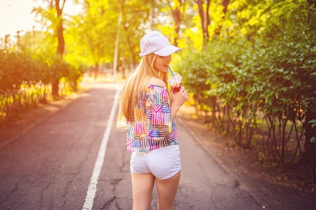 Pretty confident blonde in cap and summer outfit holding chocolate drink in cup looking at camera with smile in nature