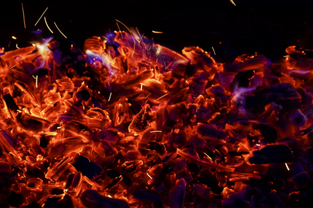 Burning firewood in the fireplace close up, BBQ fire, charcoal background. Charcoal fire with sparks Stock Photo - 107353729