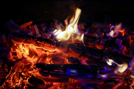Burning firewood in the fireplace close up, BBQ fire, charcoal background. Charcoal fire with sparks Stock Photo
