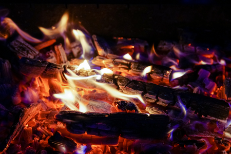 Burning firewood in the fireplace close up, BBQ fire, charcoal background. Charcoal fire with sparks Stok Fotoğraf