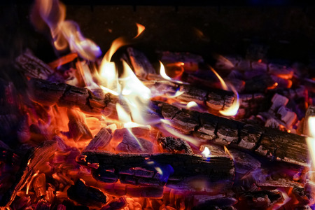Burning firewood in the fireplace close up, BBQ fire, charcoal background. Charcoal fire with sparks Stock Photo - 107353736