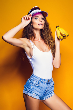 Sexy Woman in white swimsuit and blue jeans shorts, trendy visor holding bananas and posing isolated over yellow background Stok Fotoğraf
