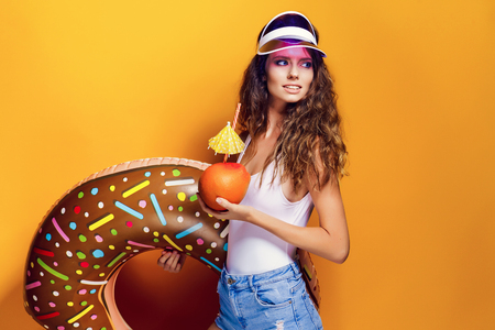 Side view of attractive young Sexy Woman in white swimsuit and blue jeans shorts, trendy visor holding fresh drink and donut-shaped swim ring while standing on yellow background