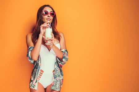 Lovely young female in swimwear and sunglasses holding glass of fresh drink while standing on yellow, orange hot background. Copyspase
