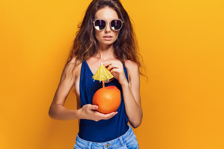Attractive young lady in summer outfit holding fresh juicy citrus with straw and umbrella and looking at camera while standing on yellow background