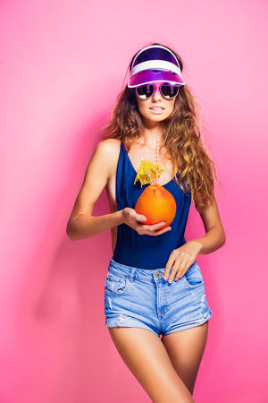 Attractive young lady in summer outfit holding fresh juicy citrus with straw and umbrella and looking at camera while standing on pink background