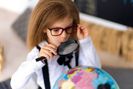 Portrait of a beautiful young schoolgirl girl exploring the globe through a magnifier. day of knowledge. beginning of the school year. studying geography with globe