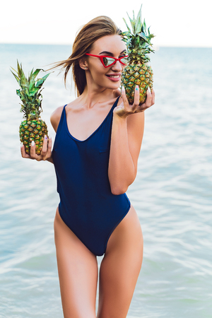 incredibly beautiful sexy girl model in a monokini on the sea shore of a tropical island holding two pineapples, bronze tan, travel summer vacation, fashion style