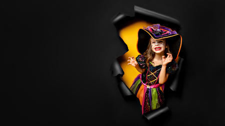 Happy Halloween. Laughing funny child girl in a witch costume of halloween looking, smiling and scares through a hole of black and yellow paper background. Copyspace Stock fotó