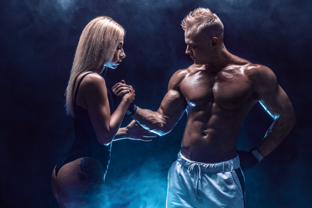 Attractive couple, a slim blonde female and handsome shirtless guy posing in studio on a dark textured background with smoke.
