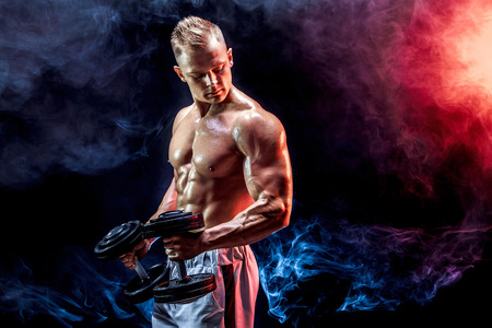Topless man exercising biceps with dumbbells posing in studio full of colored smoke