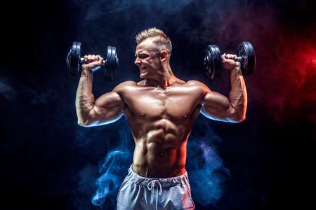 Handsome bodybuilder doing Exercise for the shoulder muscles. Studio shot.