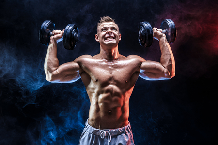 Handsome bodybuilder doing Exercise for the shoulder muscles, deltoid with dumbbell. Studio shot. Smoke. Stock Photo