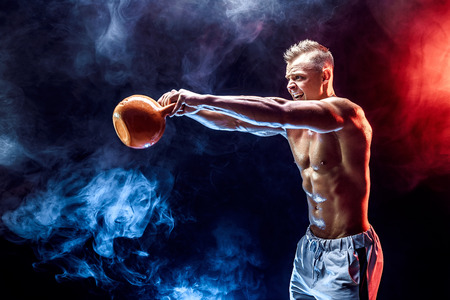 Handsome bodybuilder doing Exercise for the shoulder muscles, deltoid with kettlebell. Studio shot. Smoke.