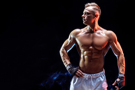Handsome strong bodybuilder posing in studio on colored smoke background Stockfoto