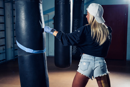 Concentrated blonde woman doing a fitness boxing workout with a punching bag. The girl in the boxing hall emotionally beats the boxing bag