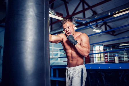 Male boxer training with punching bag in dark sports hall. Young boxer training on punching bag. Male boxer as exercise for the big fight. Boxer hits punching bag. 版權商用圖片 - 109401475