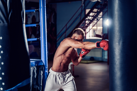 Male boxer training with punching bag in dark sports hall. Young boxer training on punching bag. Male boxer as exercise for the big fight. Boxer hits punching bag. 版權商用圖片 - 109401480