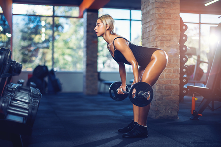 Sexy athletic girl working out in gym. Fitness woman doing exercise with barbell. Deadlift. Sexy beautiful butt 写真素材