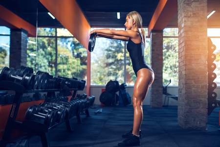 Sexy athletic girl working out in gym. Fitness woman doing exercise with dumbbell. Sexy beautiful butt