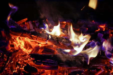 Burning firewood in the fireplace close up, BBQ fire, charcoal background. Charcoal fire with sparks 스톡 콘텐츠
