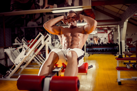 sport, fitness, bodybuilding, lifestyle and people concept - young man doing sit-up abdominal exercises Bench Press in gym Banco de Imagens