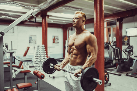 very power athletic guy bodybuilder , execute exercise with dumbbells for biceps Stock Photo