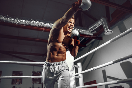 Boxer. Confident young boxer punching, training on the boxing ring Stock fotó
