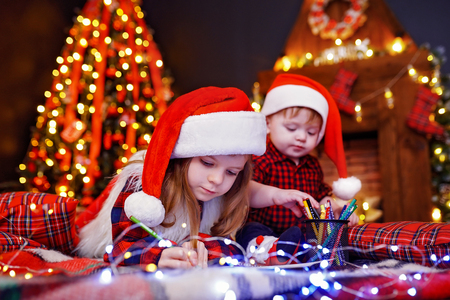 Charming girl in Santa hat lying on the floor and writes letter, draws with pencil and her little brother who interferes with her, plays with pencils in warm room with garlands, lights Stock Photo