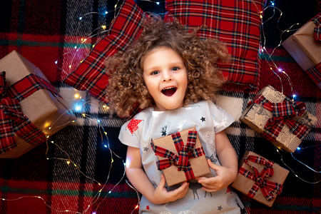 Closeup portrait of smiling cute little child in holiday christmas pajamas holding gift box. Top view of happy kid laying on checkered plaid near presents.