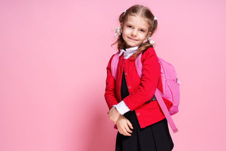 Back to school. Child with schoolbag. Schoolgirl 7-8 years old in a red jacket, white shirt, pigtails, black sarfan, school uniform with school bag isolated on pink Banque d'images - 114590387