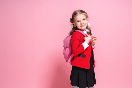 Back to school. Child with schoolbag. Schoolgirl 7-8 years old in a red jacket, white shirt, pigtails, black sarfan, school uniform with school bag isolated on pink Banco de Imagens