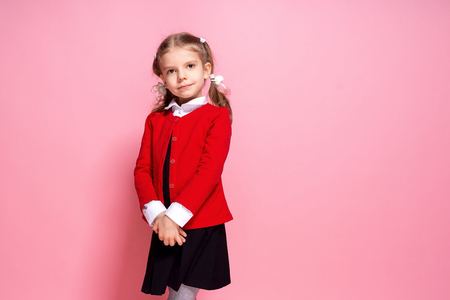 Adorable little girl in red school jacket and black dress looking at camera while standing on pink background