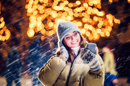 A beautiful young woman or girl doing selfie or using phone outdoors in front of Christmas holidays decorations. Selective focus on phone.