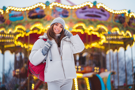 Outdoors lifestyle fashion portrait of stunning girl walking on the holiday city. Smiling and enjoying life. Wearing stylish coat, hat and red bag. Festive mood