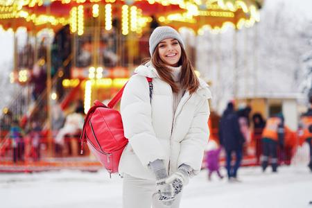 Outdoors lifestyle fashion portrait of stunning girl walking on the holiday city. Smiling and enjoying life. Wearing stylish coat, hat and red bag. Festive mood