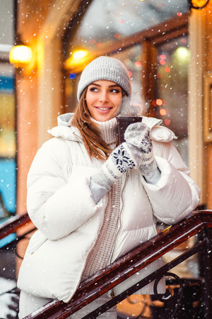 Outdoors lifestyle fashion portrait of stunning girl walking on the holiday city. Smiling, drinking coffee and enjoying life. Wearing stylish coat, gray hat. Festive mood Stock Photo