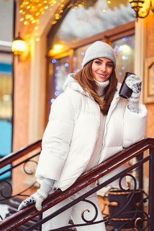 Outdoors lifestyle fashion portrait of stunning girl walking on the holiday city. Smiling, drinking coffee and enjoying life. Wearing stylish coat, gray hat. Festive mood Stock fotó