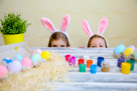 Curious small girls in bunny ears peeking out from behind kitchen table with tasty easter eggs and looking at camera with surprise. Focus on children Standard-Bild