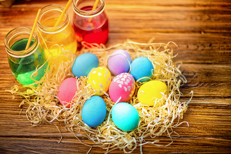 Background with colorful eggs in in straw, paints, brushes. Wooden table decorating for holiday. Top view. Stock Photo - 116353271