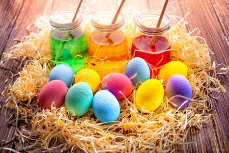 Background with colorful eggs in in straw, paints, brushes. Wooden table decorating for holiday. Top view.