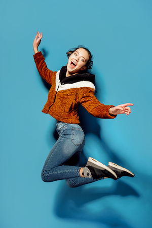 Smiling young woman jumping in air over blue background. happiness, freedom, motion and people concept .