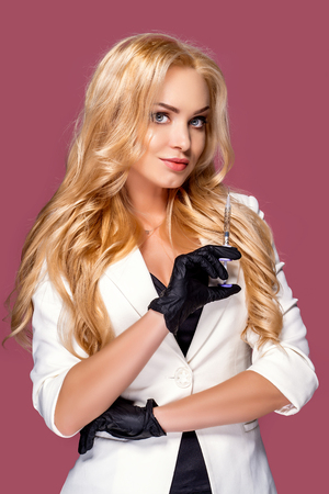 woman business lady wearing a white jacket holding a syringe with a remedy on a pink background. Concept of confident independent business woman Reklamní fotografie