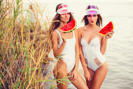 Young slim brunettes in pink caps and white swimwear standing together with slices of watermelon on shore Stock Photo