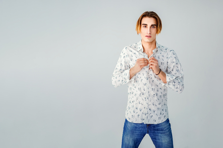 Fashion portrait of young man in white shirt poses over grey wall.