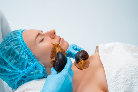 Young woman undergoing treatment with giant Achatina snails in beauty salon. Stock Photo