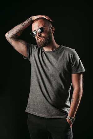 Portrait of a handsome man with long well trimmed beard wearing sunglasses and grey shirt, hold hand on head. Stock fotó