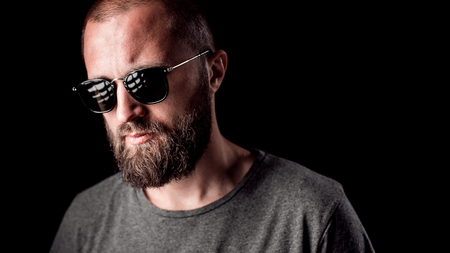 Portrait of a handsome balded man with long well trimmed beard wearing sunglasses and grey shirt. Stock fotó