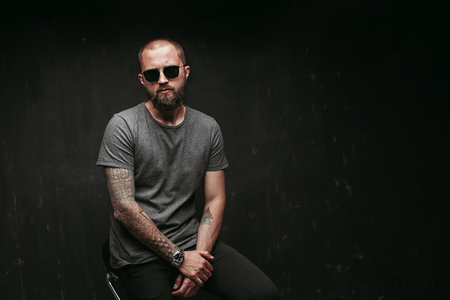 Portrait of a handsome balded man with long well trimmed beard wearing sunglasses and grey shirt looking at camera.